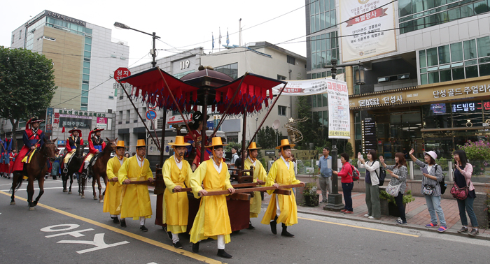 Japanese tourist Sidara Hiromi (設樂诰美) (second from right), visiting Korea to see the 2017 King Jeongjo Tomb Parade, waves to Lady Hyegyeong's palanquin as it passes exit No. 9 of Jongno 3-ga Station, in Seoul on Sept. 23.