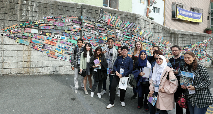 Korea.net honorary reporters pose for a commemorative photo in front of the 'Fish Travels the Alleys' mural by artist Jin Yeong-seop, at the Gamcheon Culture Village in Saha-gu District, Busan, on Oct. 26.