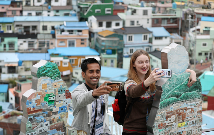Majid Mushtaq from Pakistan (left) and Elena Kubitzki from Germany have fun taking selfies next to a signature sculpture against the backdrop of colorful houses at the Gamcheon Culture Village in Saha-gu District, Busan, on Oct. 26.