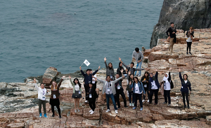 Korea.net honorary reporters wave from Taejongdae, above the blue sea, a historic site where Silla King Taejong Muyeol is said to have practiced his archery.