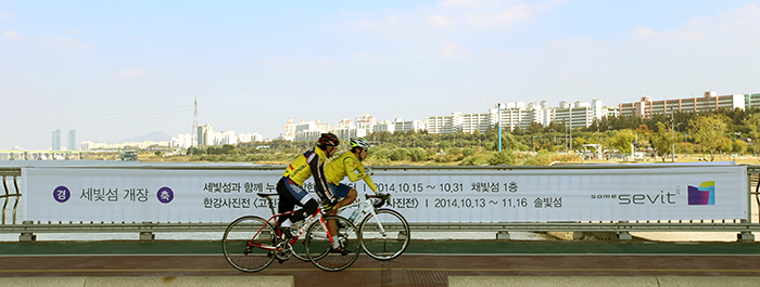 Two bicyclists ride along the Jamsu Bridge, the lower level of the Banpo Bridge, on October 15, as they pass a banner advertising the opening of the Some Sevit floating buildings.