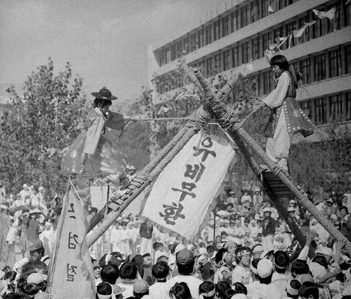 A photo from 1978 shows students partaking in Chajeon Nori, a traditional Korean game said to originate in Andong that is similar to jousting. Two players, one from each team, are carried atop wooden frames by their teammates (photo courtesy of the National Archives of Korea).