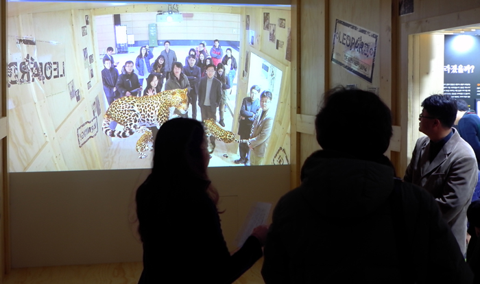 """Visitors touch a virtual leopard using 3-D computer graphics at the """"Forgotten Name, Korean Leopards"""" exhibition."""
