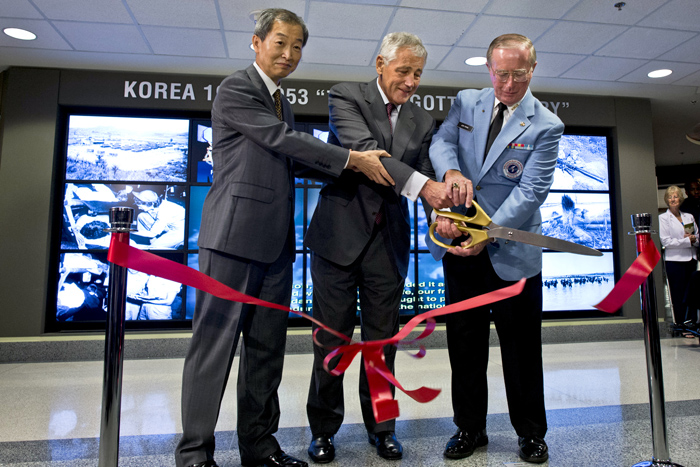 "(From left) Korean Ambassador to the U.S. Ahn Ho-young, U.S. Defense Secretary Chuck Hagel, and Lewis M. ""Lew"" Ewing, national director of the Korean War Veterans Association, cut the ribbon to celebrate the opening of the Korean War exhibit (photo courtesy of American Forces Press Service)."