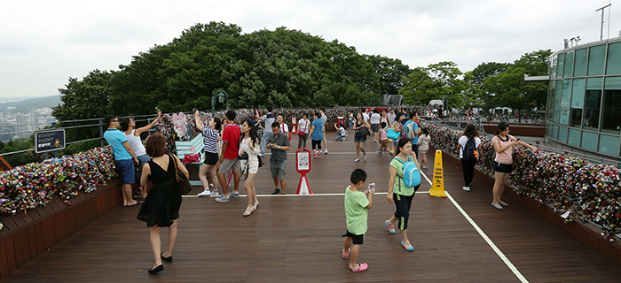 Despite the cloudy weather signaling the approach of the monsoon season, many sightseers and tourists visit N Seoul Tower and take photos of themselves and the 'padlocks of love' on July 22. (photo: Jeon Han)