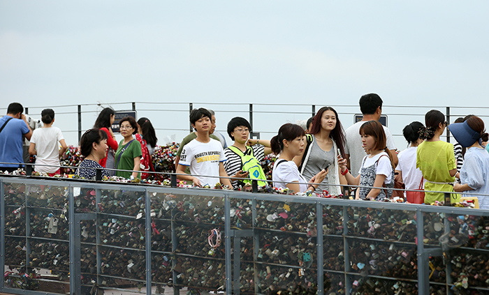 Tourists at N Seoul Tower take photos with the 'padlocks of love' and the heart-shaped chairs. (photo: Jeon Han)