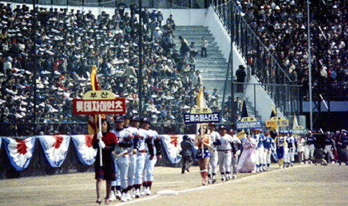 Korea's first professional baseball teams march into Dongdaemun Stadium in 1982 for a ceremony celebrating the launch of the Korean Professional Baseball League. At the front of the procession are players for the Lotte Giants (photo courtesy of the Ministry of Public Security and Administration).