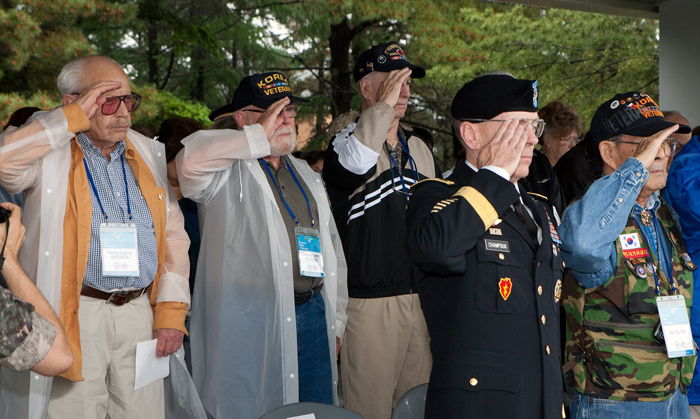 Visiting Korean War veterans stand in salute during a ceremony prepared by Korean soldiers.