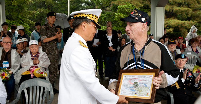 A Korean general hands over an appreciation plaque to a U.S. veteran.