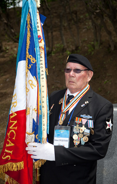 A Korean War veteran from France enters the event holding the French battalion flag.