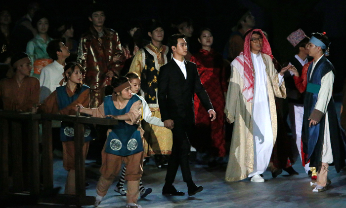 A young performer (top) rolls a hoop in the hope of unifying all Asian countries and mankind as a whole, during the opening ceremony of the Incheon Asian Games 2014 on September 19. Actor Kim Soo-hyun (bottom, center) appears on stage, holding her hand.