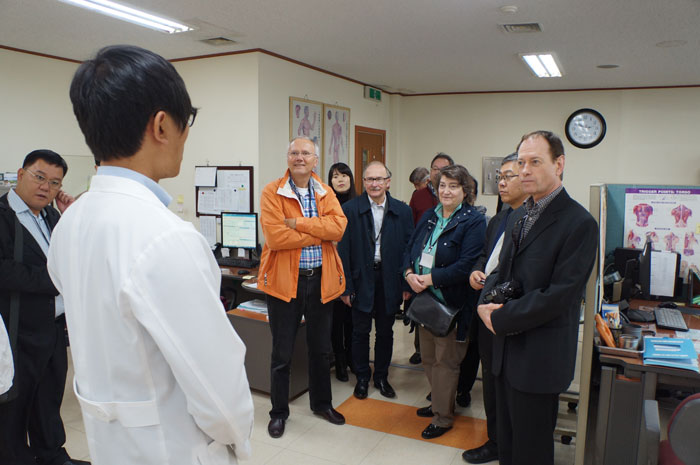 Workshop participants talk with a staff member at an Oriental medicine hospital in Korea.