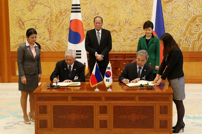 Korean Minister of Culture, Sports and Tourism Yoo Jin-ryong (seated, right) and Foreign Minister of the Philippines Albert del Rosario sign an MOU on cooperation in the sports sector, as President Park Geun-hye (back, right) and Filipino President Aquino observe from behind on October 17. (Photo: Cheong Wa Dae)