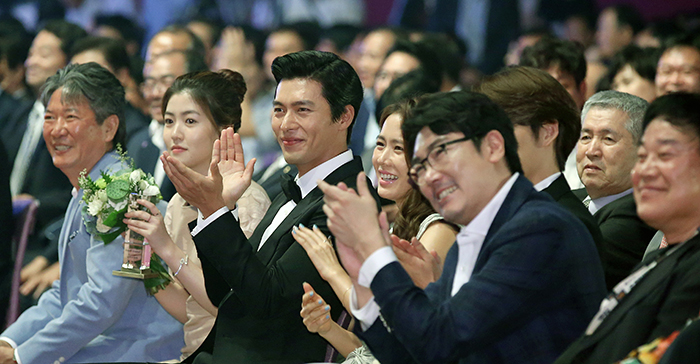 Movie stars, including Shim Eun-Kyuong (second from left), Hyun Bin (third from left) and Son Ye-jin (fourth from left), give a big round of applause during the Pifan opening ceremony hosted by emcees Shin Hyun-joon and Yoo In-na on July 17. (photo: Jeon Han)