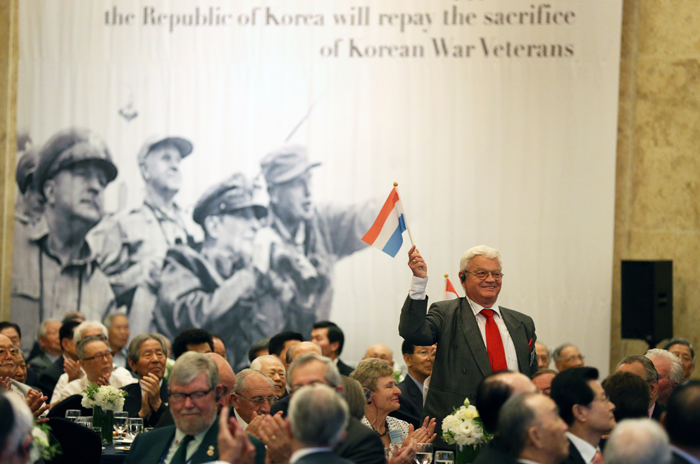 Cornelis P. Motshagen, a war veteran from the Netherlands, stands up and waves a Dutch national flag at the reception for Korean War veterans (photo: Jeon Han).