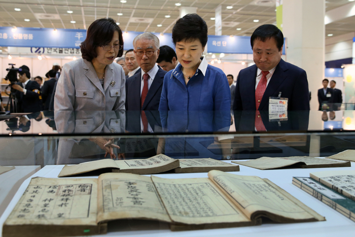 President Park Geun-hye (center) examines a display of books printed with various metal types from the Joseon Dynasty (1392-1910) at Seoul International Book Fair on June 19 (photo: Jeon Han).
