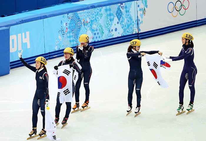 The ladies' short track team waves to the spectators as it does its celebratory lap around the ice rink holding the Taegeukgi at the Sochi Olympics on February 18. (photo courtesy of the Korean Olympic Committee)