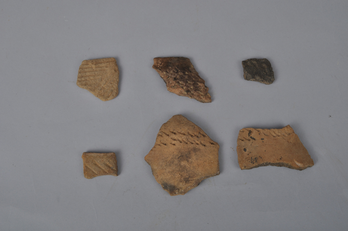 (Top) A stone-lined chamber from the Three Kingdoms Period. (Bottom) Broken pieces of earthenware from the Neolithic era are found underneath the tomb. (photos courtesy of the CHA)