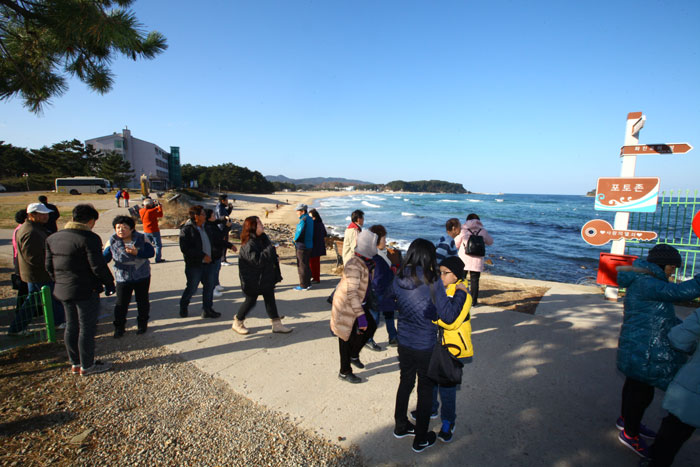 Singaporean tourists look around Hwajinpo Beach along the East Sea on Nov. 29.