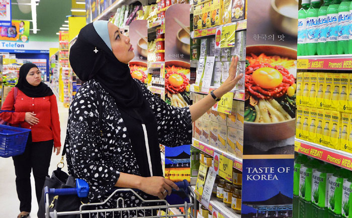 "About 20 Korean food companies that received halal certification participate in the 'Taste of Korea' event, held at 20 Tesco locations across Malaysia from late November to early December last year. In the above photo, Malaysian customers at the Tesco Mutiara Damansara store peruse Korean food products during the 'Taste of Korea"" event."