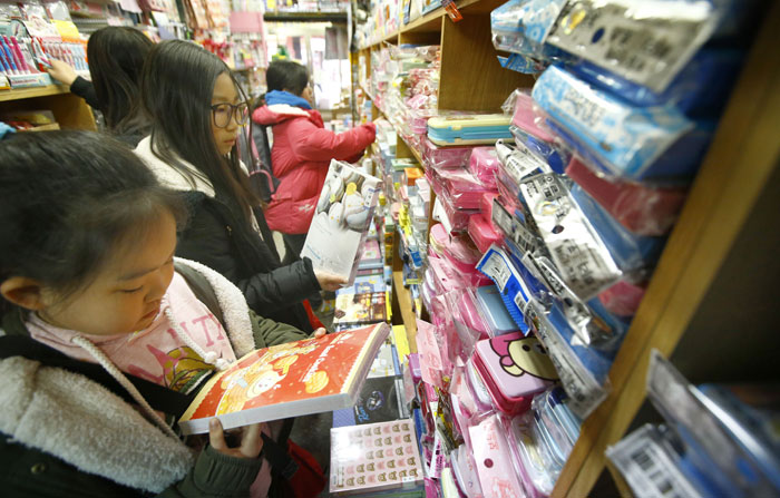 Young students peruse the stationery goods for sale at a shop in the Stationery and Toys Wholesale Market before starting a new semester or a new grade.