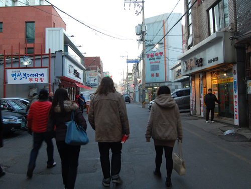 Pedestrians walking through Uijeongbu's Budae Jjiggae Street are beckoned by restauranteurs to come in and try the signature dish.
