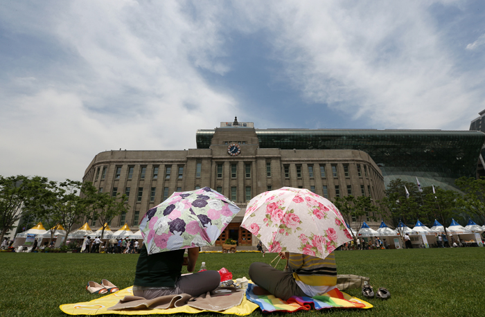 Picnickers enjoy their lunch on the grass of Seoul Plaza in front of Seoul Metropolitan Library and City Hall, downtown Seoul, on May 31 (photo by Jeon Han).