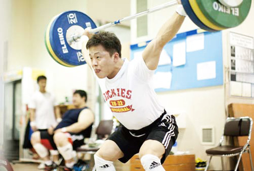 The weightlifting gymnasium is heated with practicing athletes