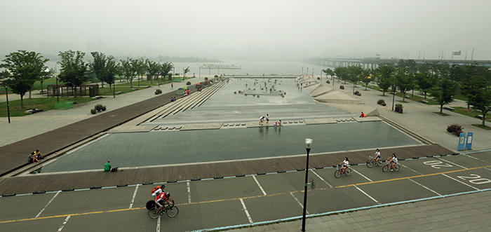 Park-goers enjoy the bike path and the giant fountain at the riverside Mulbit Square in Yeouido, Seoul, amid foggy, humid weather on August 5. (photo: Jeon Han)
