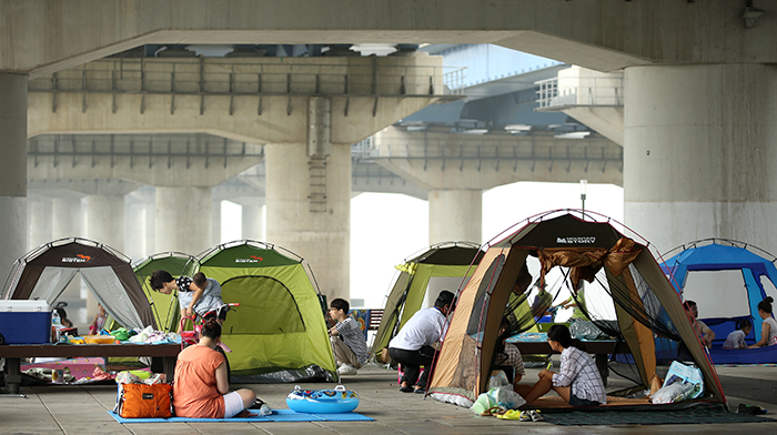 Families set up their tents under the Mapo Bridge along the riverside in Yeouido to fight off the sweltering heat during the dog days of summer on August 5. The riverside is the best refuge in Seoul during the tropical nights. (photo: Jeon Han)