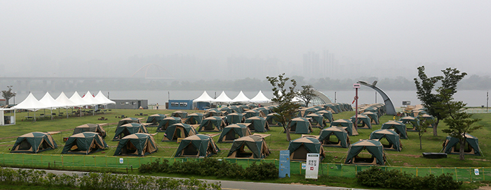 Vacationers can rent a tent for a night along the riverside in Yeouido. Without going far away, people can still enjoy their summer vacation in the city with friends and family. (photo: Jeon Han)