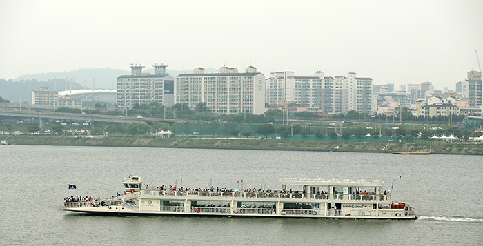 A river cruise ship along the Hangang River steams by a lookout platform at Seonyudo Park. Many people ride the ferry to overcome the sweltering heat. (photo: Jeon Han)