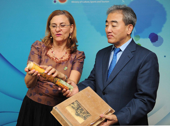 Minister of Culture, Sports and Tourism Yoo Jinryong (right) receives books and brochures about tourism in Romania from Minister Delegate for SMEs, Business Environment and Tourism Romania Maria Grapini on August 22 (photo courtesy of MCST).