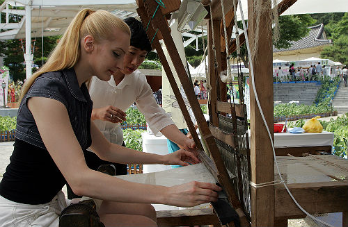 A foreign tourist participates in a hands-on ramie fabric-weaving activity offered at the Hansan Mosi Cultural Festival (photo courtesy of Seocheon County).