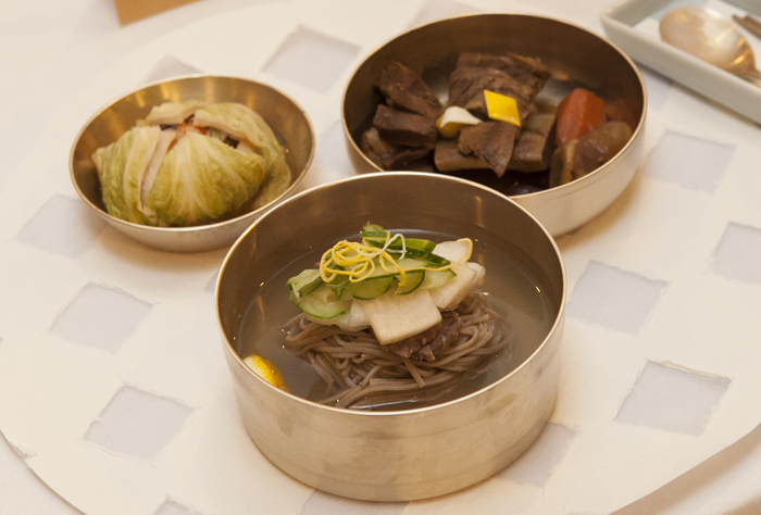 (From top, clockwise) Braised short beef ribs, kimchi, noodles in radish and pear water kimchi broth.