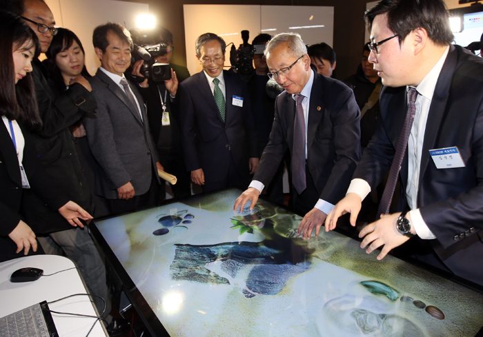 Deputy Prime Minister and Minister of Strategy and Finance Hyun Oh-seok tests a touch screen on his visit to i-KAIST (photo: Yonhap News).