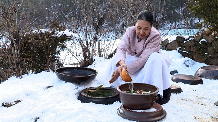 A woman collects her kimchi from large underground winter storage jars. (photo courtesy of the CHA)