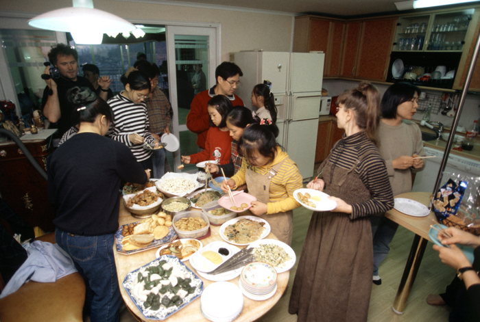 Foreign lodgers dine with their host family while staying at a Korean family house (photo: Yonhap News).