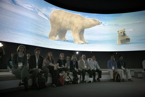 Visitors to the Climate and Environment Pavilion watch a presentation on the effect of climate change on polar bears and their habitats