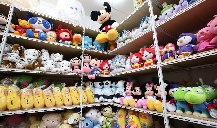 Toys of all kinds, shapes and sizes, ranging from cartoon characters to dolls, cars and stuffed animals, wait for a happy shopper to take them home.
