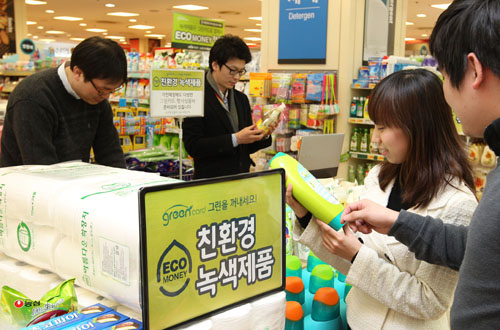 Shoppers inspect household products for labels indicating levels of eco-friendliness and carbon footprint scores. Purchase of products certified by the GreenCard initiative qualifies shoppers to receive eco-money points